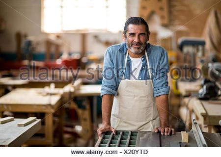 Carpenter standing in workshop - Stock Photo