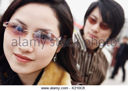Portrait of a young woman wearing sunglasses - Stock Photo