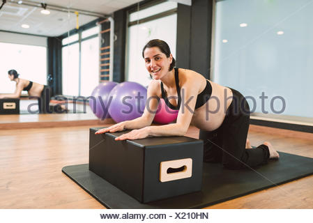 Pregnant woman doing Pilates exercises in a gym - Stock Photo