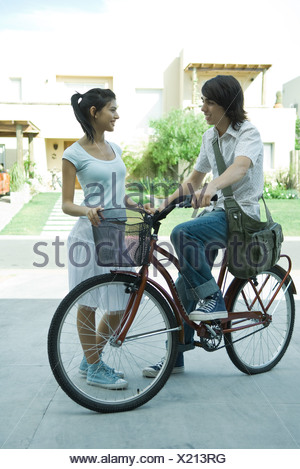 Teen boy on bike speaking to young female friend in residential neighborhood, full length - Stock Photo