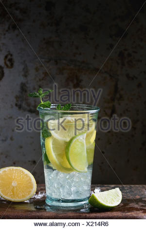 Homemade lemon and lime lemonade, served in glass  with ice and fresh mint, oveer dark iron rusty background. With space for tex - Stock Photo