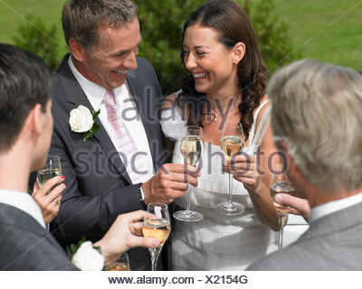 Bride and groom with wedding guests - Stock Photo