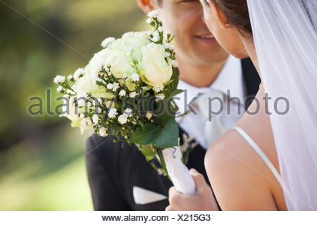 Mid section of a newlywed couple with bouquet in park - Stock Photo