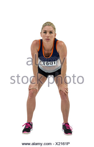 Tired athlete standing with hand on knee - Stock Photo