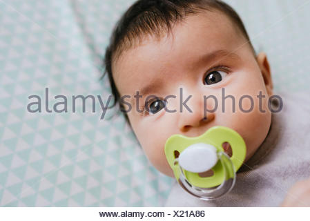 Portrait of baby girl lying on bed sucking a pacifier - Stock Photo
