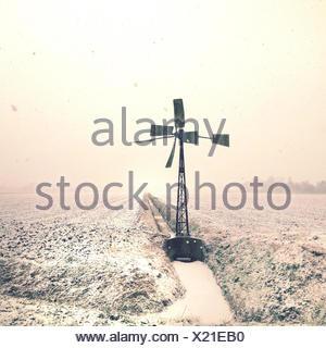 Wind turbine on field at winter - Stock Photo