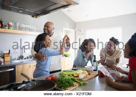 African American parents dancing and cooking with children in kitchen - Stock Photo