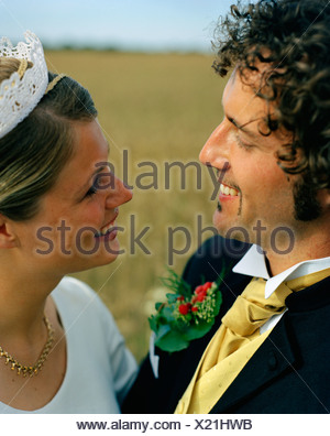 Scandinavia, Sweden, Oland, Bride and groom smiling at each other, close-up - Stock Photo