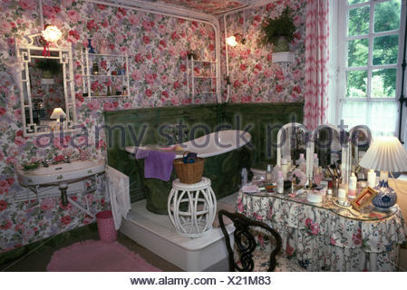 Slipper bath on small platform in corner of eighties bathroom with rose patterned wallpaper - Stock Photo