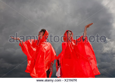 Women in ponchos feeling for rain - Stock Photo