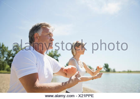 Middle-aged couple performing tai chi on beach - Stock Photo