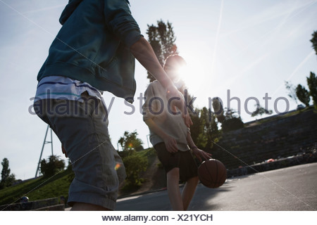 Germany, Berlin, Teenage boys playing basketball in playground - Stock Photo
