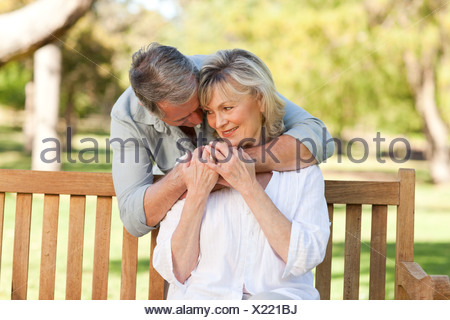 Elderly man hugging his wife who is on the bench - Stock Photo