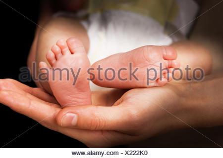 moms hands holding baby's feet - Stock Photo