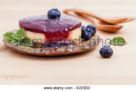 Blueberry cheesecake with fresh mint leaves on wooden background - Stock Photo