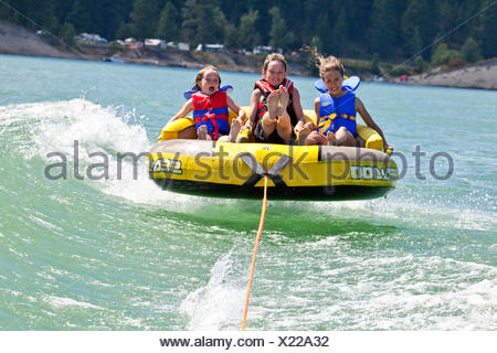 Three children enjoy tubing on Lake Koocanusa, East Kootenays, BC, Canada. - Stock Photo
