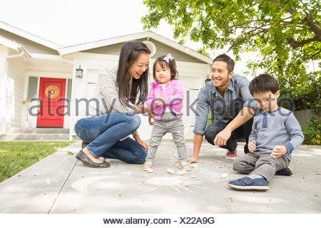 Mid adult couple with two children drawing on paving slabs - Stock Photo