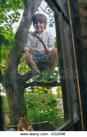 Two boys playing in tree outside hut window - Stock Photo