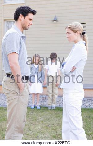 Portrait parents arguing with unhappy children background - Stock Photo