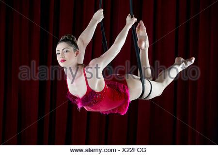 Studio shot of female aerialist balanced on rope - Stock Photo