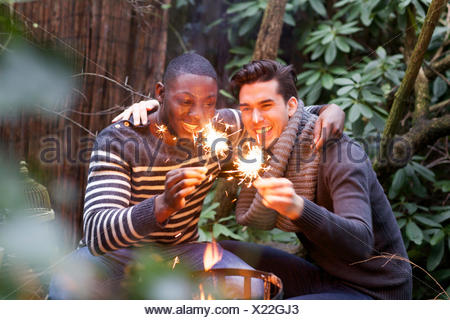 Two young men crouching in front of garden fire with sparklers - Stock Photo