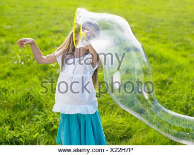 Little girl making soap bubbles - Stock Photo
