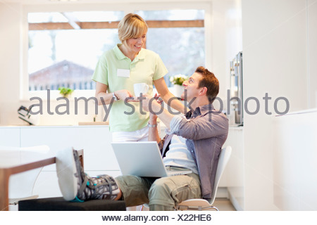 Mid adult man in foot brace using laptop, woman bringing him coffee - Stock Photo
