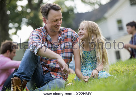 A far and daughter at a summer party sitting on  grass. - Stock Photo