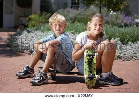 Boy 7 9 and girl 8 10 sitting on brick driveway holding skateboards smiling portrait - Stock Photo