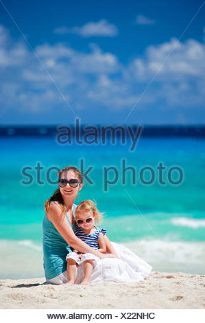 young mother and her daughter sitting on sandy beach - Stock Photo
