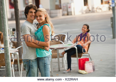 Germany, Munich, Couple at cafe with woman in background - Stock Photo