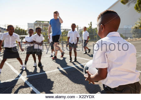 Teacher plays football with young kids in school playground - Stock Photo