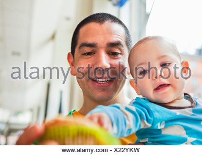 Father sitting with daughter (0-11 months) at coffeehouse - Stock Photo