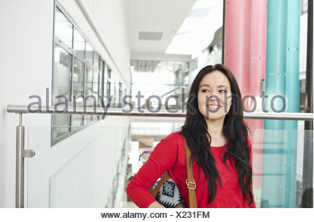 Young woman with long black hair smiling, portrait - Stock Photo