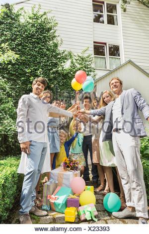 Portrait of three generation family holding up birthday balloons in garden - Stock Photo