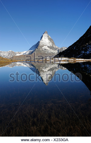 Matterhorn reflected in Lake Riffelsee, Zermatt, Valais, Switzerland, Europe - Stock Photo