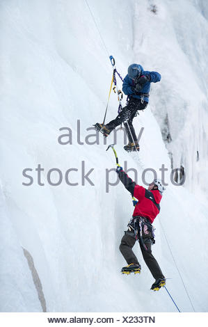 A photographer photographs an ice climber in Calif. - Stock Photo