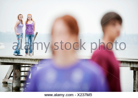 Germany, Bavaria, Ammersee, Two women standing on jetty, man in foreground - Stock Photo