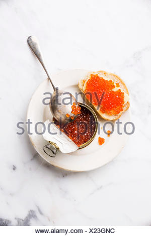 Salmon red caviar in can and sandwich on white marble background - Stock Photo