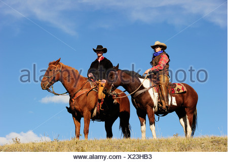 Cowgirl and cowboy on horses looking into the distance, Saskatchewan, Canada, North America - Stock Photo