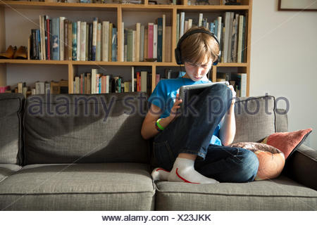 Boy listening to music on headphones and using digital tablet - Stock Photo