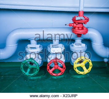 Germany, Hamburg, Yellow, red and green valves on a container ship, close up - Stock Photo