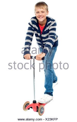 Smart looking kid riding on his zippy cycle. Causal random shot - Stock Photo