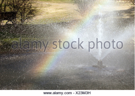 Rainbow stretching over a fountain, Ahlbeck, Germany - Stock Photo