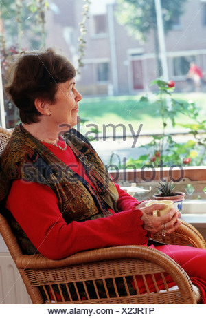 Female pensioner sitting on chair looking out of window, cup of coffee in hands, thinking - Stock Photo