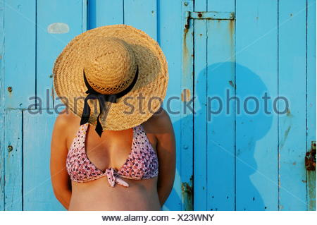 Pregnant woman wearing a straw hat - Stock Photo