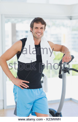 Portrait of a smiling man at spinning class in bright gym - Stock Photo
