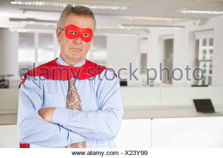 Portrait of serious businessman in superhero costume in office - Stock Photo