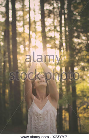 Portrait of a woman standing in forest catching sunlight in her hands, Mississippi, America, USA - Stock Photo