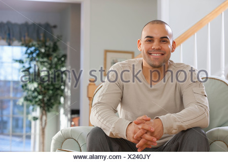 Hispanic man sitting in an armchair and smiling - Stock Photo
